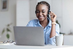 Customer Support. Black woman manager wearing headset and using laptop in office